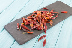 Red Dried Chillies. Dry chillies on a slate in a blue background Stock Image