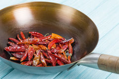 Red Dried Chillies. Dry chillies in a wok on a blue background Stock Images