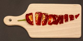 Red dried pepper slices, cut piece of pepper on wood cutting board. Vegetarian diet Stock Photo