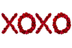 Red dried rose petals arranged into xoxo Royalty Free Stock Images