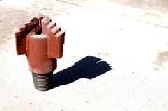 A red drill bit or rock bit on concrete. Stock Images