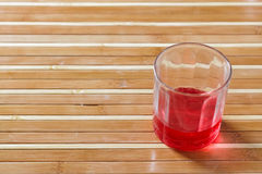 Red drink on bamboo floor Stock Image