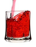 Red drink is being poured into glass. Isolated over white Stock Images
