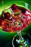 Red drink on green with cherries Royalty Free Stock Images