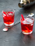 Red drink with ice. Cocktail making bar tools, strawberry and thyme leaves Stock Photography