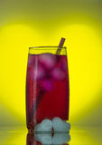Red drink with ice on a yellow background Stock Image