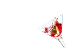 Red drink with lime falling into glass Stock Photography