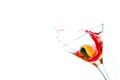 Red drink with lime. Falling into glass. Food and drink background, alcohol Royalty Free Stock Photography