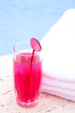 Red drink at the pool with white towel Stock Photo
