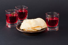 Red drink with potato chips Royalty Free Stock Images
