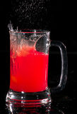 Red drink with a splash on a beer glass Stock Image