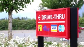 Red drive-thru sign with traffic flow background stock video