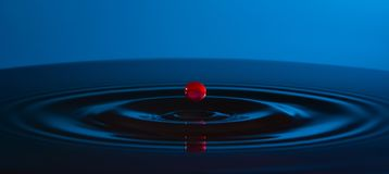 Red drop of water and circles on the water on blue background. stock image