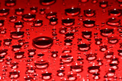 Red droplets. Droplets of water on a red glass surface Royalty Free Stock Image