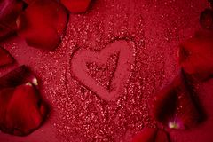 Red drowing heart on red background with red roses petals royalty free stock photos