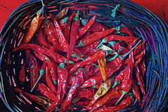 Red dry chili peppers in straw basket Royalty Free Stock Photo
