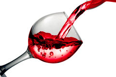 Red dry wine pours into a wineglass on a white background Stock Photos