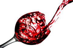 Red dry wine pours into a wineglass on a white background Stock Photography