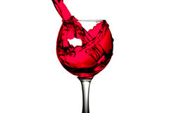 Red dry wine pours into a wineglass on a white background Stock Photo