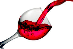 Red dry wine pours into a wineglass on a white background Stock Images