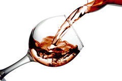 Red dry wine pours into a wineglass on a white background Stock Image