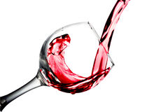 Red dry wine pours into a wineglass on a white background Royalty Free Stock Photo
