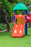 Red Dual Slides for Children on Green Lawn. Schoolyard Stock Images