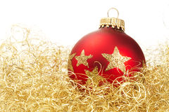 Red dull christmas ball in golden glitter cotton. On white background royalty free stock photo