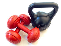 Red dumbbell and black kettlebell. 5lb Red dumbbells and a 10lb black kettlebell on white background Royalty Free Stock Photography
