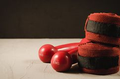 Red dumbbells and bandage/red dumbbells and bandage on a black background. Selective focus and copyspace. Boxing equipment boxer concrete stone exercise stock photography