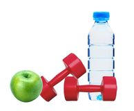 Red dumbbells fitness, apple and bottle of water Royalty Free Stock Photo
