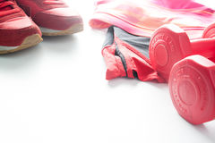 Red dumbbells and sport wear in fittness background. Sport wear,. Sport fashion, Sport accessories, Sport equipment Stock Photo