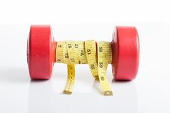 Red dumbbells weight with measuring tape Stock Image