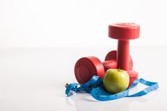 Red dumbbells weight with measuring tape and green apple Stock Image