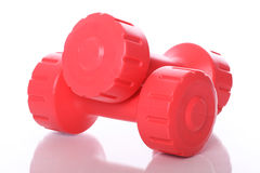 Red dumbells over white background Stock Images