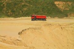The red dump truck leaves a sandpit. POLEWOJE, KALININGRAD REGION, RUSSIA — JUNE 18, 2014: The red dump truck leaves a sandpit Stock Image