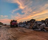 Red Dump Truck Near Filed Rocks Under Cloudy Sky Stock Images