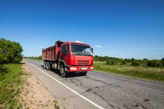 Red dump truck on a road. In summer royalty free stock image