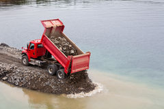 Red dump truck unloading earth fill Royalty Free Stock Images