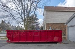 Red Dumpster Bin On The Driveway Of A Suburban House 2 Royalty Free Stock Photo