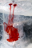 Red dye poured into water Stock Photos