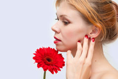 Red ear rings, nails and flower. Portrait of the young girl with red ear rings in ears, red nails and a red flower Royalty Free Stock Image
