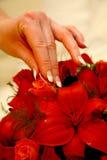 Red Earring. Woman taking earring on flower Stock Photo