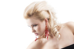 Red earring on cute blond girl, she bent Stock Photography