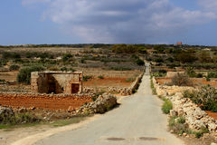 Red Earth on Malta. Road to Popeye Village with Red Keep on the horizon Stock Photos