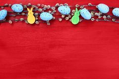 Red Easter background. Willow branch and decorative blue Easter eggs on red background. Top view Royalty Free Stock Photography