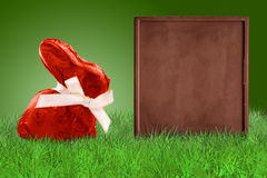 Red Easter bunny and chocolate board. Red Easter bunny and chocolate bas as a board on grass on green background Royalty Free Stock Photos
