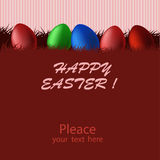 Red Easter card with eggs. Red card with colorful Easter eggs in the grass and the inscription on a red striped background Stock Photo