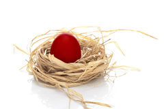 Red Easter egg. Single Easter egg in a hay nest Stock Images