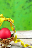 Red easter egg in basket with ribbon. Red easter egg in basket on green background Stock Images